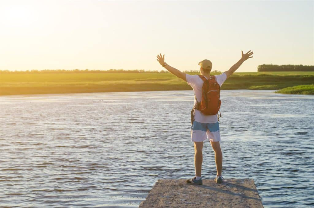 young man standing arms outstretched in front of lake