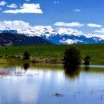 Landscape picture: river, grass, mountain, sky